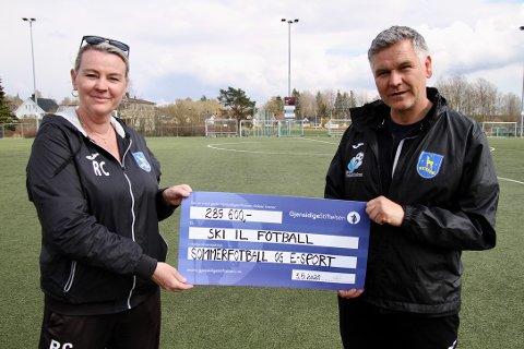 Ragnhild Carlsen og Odd-Inge Bondevik fra Ski IL fotball smiler bredt etter å ha mottatt nesten 290.000 kroner fra Gjensidigestiftelsen.