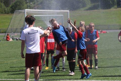 DUSJ: Ungene på Tine fotballskole på Langhus var fornøyd med at vannslangen ble tatt i bruk. Det var varmt på Langhus onsdag.