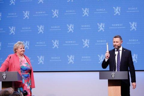 DAGEN ER KOMMET: Statsminister Erna Solberg og helseminister Bent Høie med tommestokken under pressekonferanse om koronasituasjonen fredag