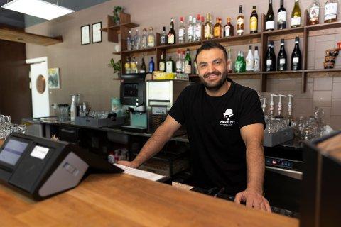 ØNSKER KUNDENE VELKOMMEN: Abdulaziz Sharro ved Charlies Diner Ås ønsker kundene velkommen med et smil.
