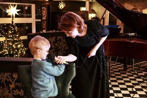 Hjelp: Cecilie Schilling overrekker mikrofonen til sønnen sin, og får vokal hjelp.foto: rolf mikkel johansen