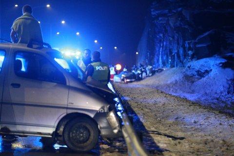 DØDSKRASJET: Her jobber redningsmannskapet for å få ut de skadde av bilen 1. januar 2018, mens den tiltalte 22-åringen (t.v.) sitter på biltaket og ser på.