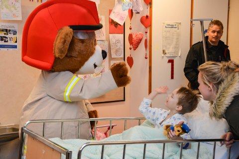 HIGH FIVE, BJØRNIS! Matheo Ingvaldsen Tangen (5) fra Sør-Odal fikk hilse på selveste brannbamsen Bjørnis fra Barne-TV som kom på besøk på barneavdelinga på sjukehuset i Elverum.