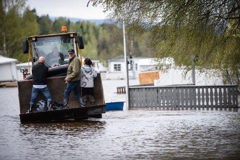 OPPGITT: Driver av Rena camping, Lars Ole Sveen blir fraktet ut i flommen for å sjekke forholdene i resepsjonen etter at Glommen fløt tvers gjennom campingplassen.