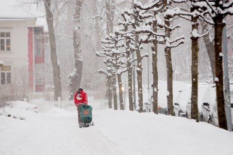 OSLO  20110210. En postmann drar posten etter seg i snøen. Snøværet over Østlandet gjorde sitt til at det ble ufyselig føre for både bilister og fotgjenere. Foto: Stian Lysberg Solum / SCANPIX