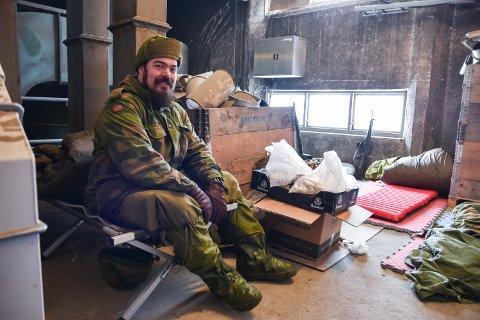 ROM: Erik Finstad sitter på feltsenga i det som er soverommet hans under øvelsen. Her sover folk i kriker og kroker.