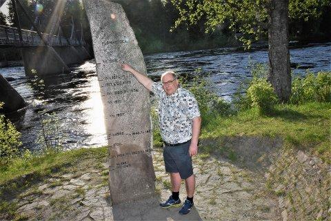 FLOMSTEIN: Daværende ordfører Per-Gunnar Sveen viser hvor høyt flommen i 1995 nådde på flomsteinen ved Skogmuseet. Storofsen i 1789 nådde nesten helt opp på toppen av flomsteinen.