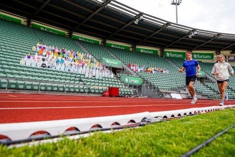 TOMME TRIBUNER: Therese Johaug og broren Karstein løper forbi de kunstige tilskuerne på Bislett stadion under trening til Impossible Games. (Foto: Lise Åserud / NTB scanpix)