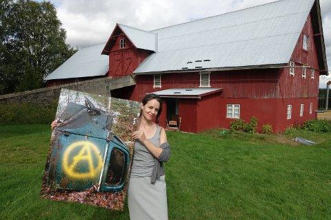 I LÅVEN: Cicilie Risåsen har laget sin egen kunsthall i låven på Våler vestside. Her er hun med et av bildene Roger Kordahl stiller ut av sin tagging på avfall i naturen.