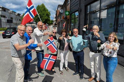FLAGG OG BOBLER: Sentrale personer i Moelv jubler over Mjøssykehuset: Erik Slaatsveen (leder i Moelv Idé og næringsforum), Tore Skar (Intersport), Dagfinn Dulsrud (Dulsrud Klær), Grethe Kongssund Sveen (Svarstad), Eivor Øen (Moelven IL), Morten Andersen (lanserte Mjøssykehuset for snart 30 år siden sammen med kamerater), Leif Østmo (sykehusforkjemper) og Lene Jægersborg (leder i handelsstanden).