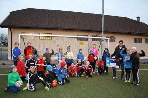 Per Tangene fra Brevik Lions deler ut en pengegave på 12.000 kroner til barnefotballen i Brevik. Det krydde av unge fotballspillere under treningen på Furulund Idrettspark mandag ettermiddag, til tross for at det blåste sur og kald vind.