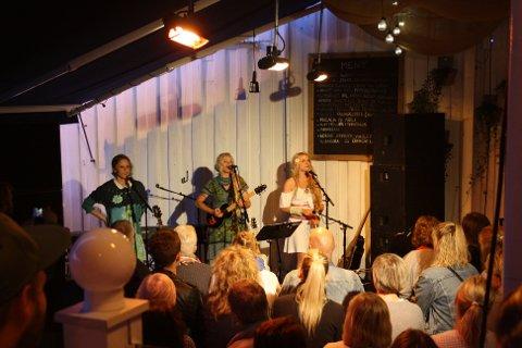 De bergtok sitt lille publikum på terrassen på Wrightegaarden, Hanne M. Karlsen, Unni Wilhelmsen og Solveig Heilo. De muntre musikerne håndterer 14 ulike instrumenter.