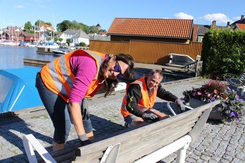 Vigdis Otterholm og Trond Gundersen pusser og maler benkene som står langs bryggekanten foran Brevik kulturhus. Trond er nestleder i Brevik vel.