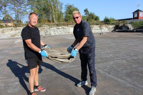 Thor Brønsten og Tom Ellis Hansen i parkstyret i Brevik Idrettslag jobber dugnad for å fjerne det gamle kunstgresset og dreneringsduken under, for å legge nytt kunstgress med gummisamlere.