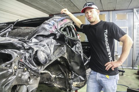 Totalvrak: Tor-Anders Ringnes poserer her sammen med den totalvrakede bilen han var uheldig og krasje med i 200 kilometer i timen. Etter forholdene har Tor-Anders det bra, men han forteller at det ikke blir mer konkurransekjøring før til neste år. Foto: Joachim C. Høyer