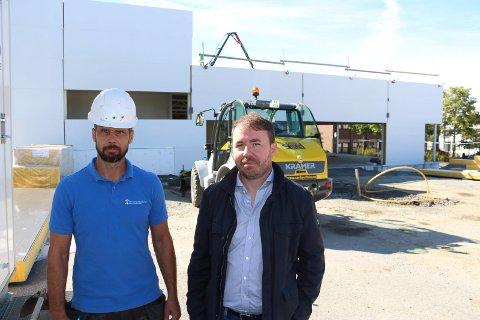 BYGGER: Steinar Skjelhaugen i Scanbygg og Vidar Sølvskudt, opprinnelig raksting og utvikling- og etableringsjef i Rema 1000 foran forretningsbygget som reiser seg i sentrum.