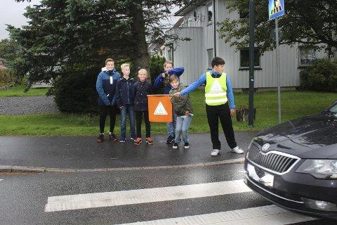 MÅ VENTE: Når det står noen og venter ved gangfeltet, skal bilene stoppe selv om skolepatruljen ikke står med flagget ut. Men med ett hederlig unntak brøt bilistene vikeplikten da Bertosz Falkowski i skolepatruljen og de andre elevene  hadde gjennomgang med politiet.