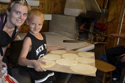 En hjelpende hånd: Marius Forsmo Sørli (6,5 år) har frivillig hjulpet til på Kamkakfestivalen hele helgen, med å bringe fat dekket av nykjevlede deigemner til ovnen. Her sammen med mamma Annette Forsmo.Foto: Beate Nygård