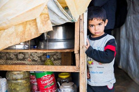 En liten gutt titter nysgjerrig fram fra et av skurene i flyktningeleiren i byen Qab Elias i Bekadalen i Libanon. I denne leiren har det bodd syriske flyktninger fra både Aleppo, Raqqa og Idlib i Syria.