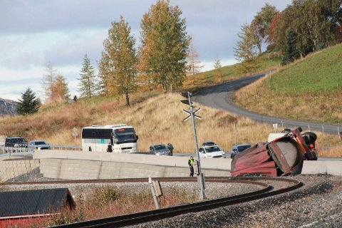 Asfaltbil av veien over jernbane rynes, brannbil. Ulykke