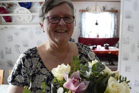 Overrasket: Gladis Berg, som til daglig jobber på Prix i Åga, er hjemme når Rana Blad kommer med blomster. Foto: Ann Kristin Kjærnli