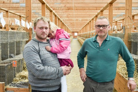 BEKYMRET FOR FREMTIDEN: Pelsdyrbøndene Kristian Aasen (39) (t.v.) med datteren Minda på armen og Magne Sørby (52) (t.h.), er bekymret for fremtiden etter regjeringens siste kompensasjonsforslag. Her fotografert i et av Sørbys minkfjøs fredag.
