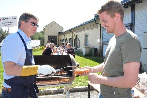 Eier og sjef Tore Persson serverer grillmat til Simen Vanem og de ansatte på Satema.
