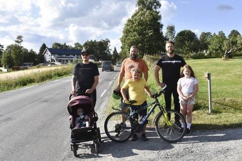 FOR BARNA: Byflatvegen mellom Brumunddal og Byflaten har et strekke på 1,6 kilometer uten gang- og sykkelveg. Nå tas det til orde for at det snarest må bygges ut slik at barn og unge kan ferdes trygt på sykkel og til fots. Bak fra venstre: Ole Christian Bækkevold (36), Håvard Fjellstad (38) og Terje Melheim (43). Foran fra venstre: Tobias (6 mndr.), Haagen Fjellstad (9) og Lily Olea Svendsen Melheim (8).