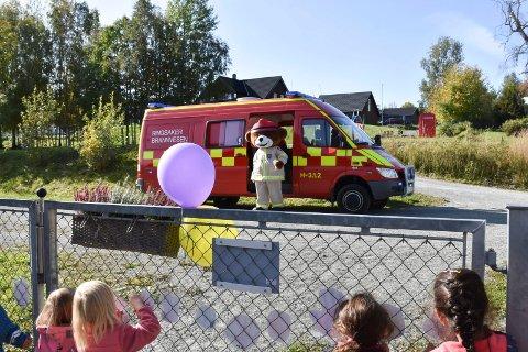 PÅ BESØK: Bjørnis stiger ut av brannbilen. Ved porten står forventningsfulle barn i Brumund barnehage.