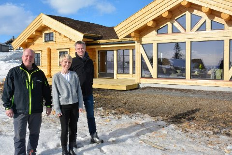 Nybygd: De er optimister for salg av denne hytta på 130 kvadratmeter. Esten Kjølvang (t.v), Hege Feiring og Eirik Fossbråten i Østlaft foran hytta som er maskinlaftet i fabrikken på Rudshøgda.