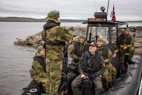OM BORD: Kronprins Haakon, forsvarsjef Eirik Kristoffersen (bak t.v), sjefen for hæren, Sivert Lervik (bak t.h) og kronprinsens livvakter om bord i båten til brøtning Mari Hallberg Bakkestuen (ryggen til) i Pasvikelva.
