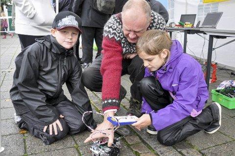 Ole Jørgen Bøhn og Vilde Blesvik Eriksen får hjelp av Per Olerud til å kontrollere et bevegelsesstyrt kjøretøy - bygget av elektro-elever på Hønefoss videregående skole.