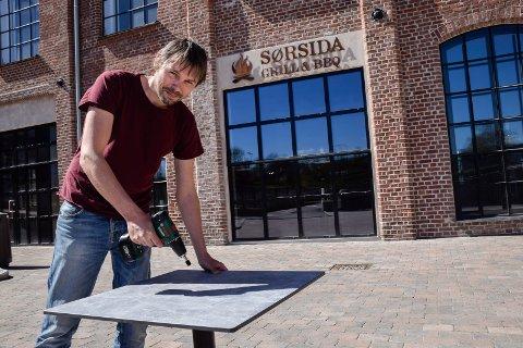 Uteservering: Jonas Gythfeldt skrur som en helt og setter opp bord og stoler utenfor Sørsida Grill&BBQ.