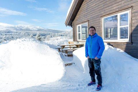 Erlend Søraker viser fram visningshytta på Skarrudåsen. Fjellområdet i bakgrunnen er nå vernet område, men ved Killingtjern er det planer om å bygge flere nye hytter.
