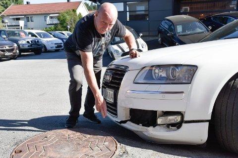 STYGGE SKADER: – Opphøyningen burde vært fylt ut, og de som har asfaltert her burde ha skjønt at det er gjort en for dårlig jobb. Helge Sjøbloms Audi fikk hard medfart i møte det kommunale kumlokket da han skulle parkere i Hønengata.