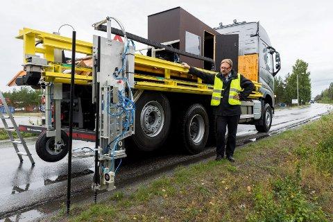 SKRUR NED STIKKENE: Henrik Petersen viser hvordan maskinen skrur brøytestikkene ned i veikanten. Dette skal maskinen kunne gjøre i fart.