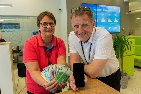 KONTANTLØST: Jo, det finnes fortsatt noen sedler i banken, slik Bente Øiseth viser her. Men betaling med mobilen er på full fart til å ta over for kontantene i hverdagen til folk flest, konstaterer banksjef Per-Arne Hanssen i Hønefoss sparebank.