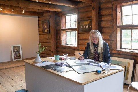 FORBEREDELSER: Galleristen Elenor har mye å gjøre før en utstilling. Det er heller ikke mange dagene mellom hver kunstner som skal stille ut. – Nå må jeg finne ut hvordan kunsten skal henge, og det følger også med litt tekst til hvert bilde, sier Elenor.