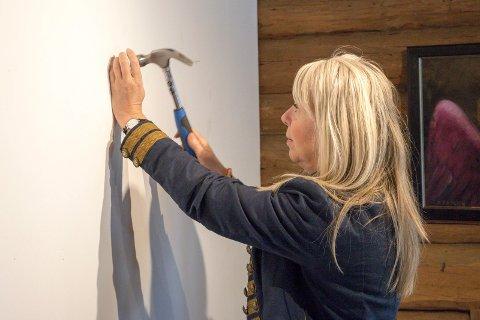 OPPGAVER: En gallerist har mange oppgaver. Å slå i spiker for å henge opp kunsten er en av dem. – Det er mye planlegging bak en utstilling, sier Elenor Martinsen.