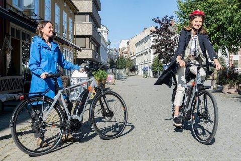 VIL AT DU TESTER SYKKEL: Ingvill Eidesen (på sykkelen) og Bente Elsrud Anfinnsen håper mange finner ut at elsykkel er et godt alternativ, etter å ha lånt sykkel fra kommunen.