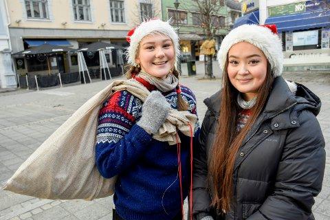 NISSEHJELP: Hanna Rustad og Sara Hermansen hjalp nissen med å dele ut godteri til barna i Hønefoss lørdag. De er to av i alt 21 jenter i en russegruppe som har tatt på seg jobben.