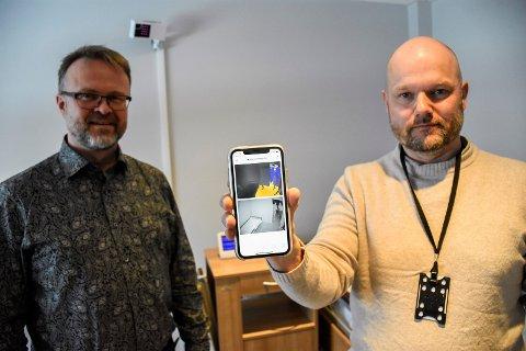 INFRARØD SENSOR: Rune G. Erlandsen (til høyre) og Tom Morten Bomstad Nilsen viser hvordan signalene fra den infrarøde sensoren, som vi ser i bakgrunnen, vises på mobiltelefonen.