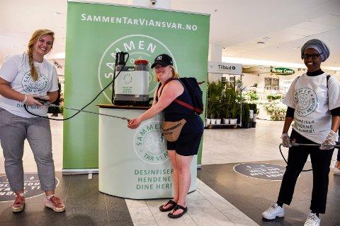 HÅNDHYGIENE: Anne Sørsdal Fodnæss får hendene desinfisert av Idun Mørch. Sammen med Sagal Qalid var hun på plass for å sørge for god håndhygiene på Kuben.