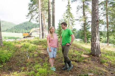 KLATREPARK: Arbeidet med Høyt og lavt-klatreparken på Søndre Kopland i Modum er i gang. Gunhild og Torger Kopland Terum står inne i skogen der klatreløypene skal bygges. Servicebygget kommer omtrent der gravemaskinen står.