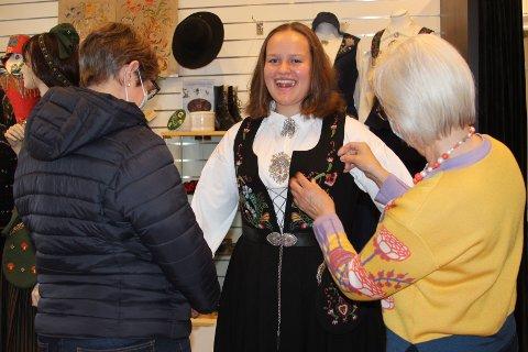 HØYTIDELIG: Thea Johansen prøver Ringeriksbunaden hun har arvet av mamma Ingunn Frogh (til venstre). May Wenche på Husfliden i Hønefoss hjelper til.