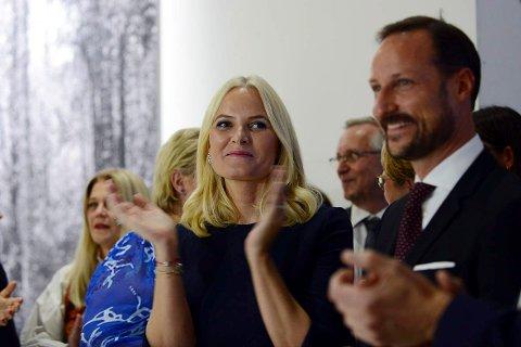APPLAUS: Kronprinsesse Mette-Marit og kronprins Haakon under åpningen av den norske avdelingen av bokmessa.  Bak skimtes et av de store bildene til Per Berntsen fra Atrå.