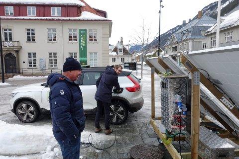 LADER: Solstråler fra solspeilet oppe i fjellsida  får fart  på elbilen nede på Rjukan torg. - Nå overføres strøm, jeg ser det på displayet her, sier Jan Erik Lauritzsen , som har bygd riggen. Henrik Ebbing  i Tinn Energi har akkurat plugget inn kontakten på elbilen.