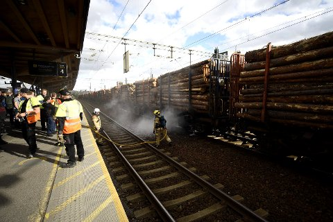 RØYKUTVIKLING: Her jobber brannvesenet med å kjøle ned vogna. FOTO: VIDAR SANDNES