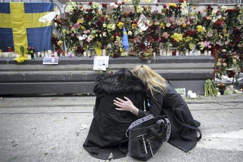 SORG: Fire personer ble drept da terroristen kjørte gjennom folkemengden i Stockholm. Her sørger to kvinner ved åstedet FOTO: AP/SCANPIX