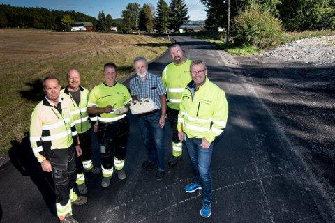 Sven Presterud, Vemund Aamodt,  Kent Hval, Terje Svea og Kjell Lund i Fet kommune har sørget for asfalt i Faldalen. Beboer Jan Erik Aamillom ble så glad for veidekket at han inviterte på kake.